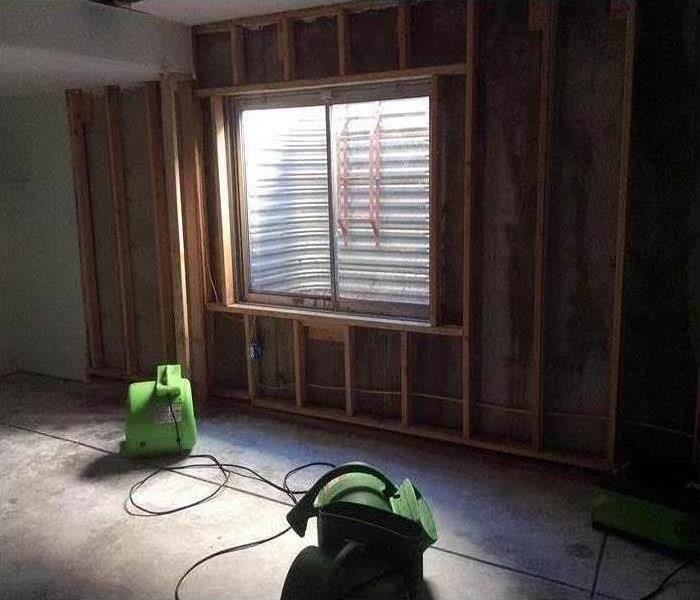 A room with drywall missing from the wall, and SERVPRO equipment on the floor.