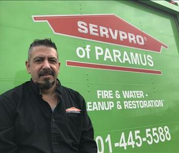 A man with a black shirt on standing in front of a SERVPRO vehicle.