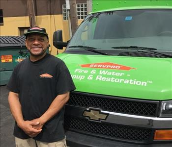 A man with a beanie on standing in in front of a SERVPRO vehicle.