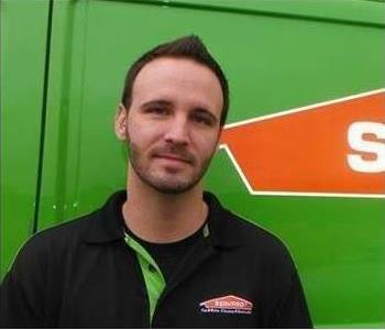 A man with a back polo on standing in front of a SERVPRO vehicle.