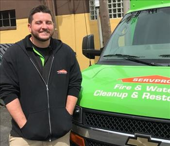An employee standing next to a SERVPRO van.