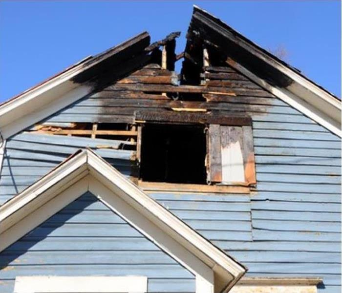 Fire damage to the top point of the outside roof of a home.