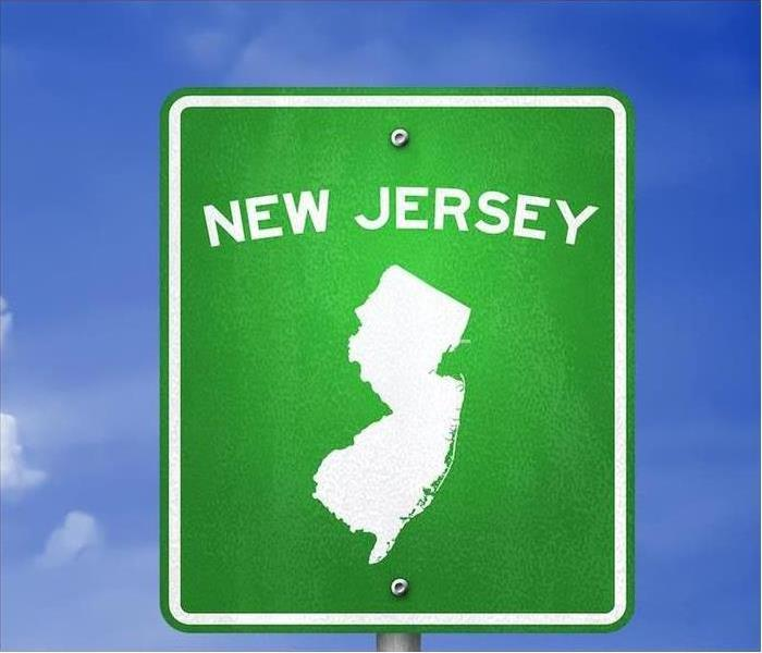 Green New Jersey road sign with a sky background