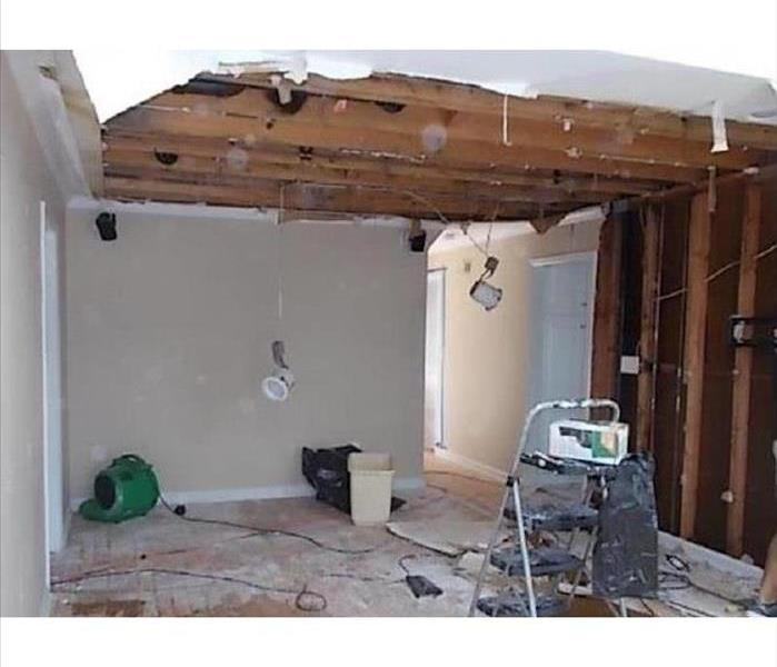 A room with drywall missing from the walls and ceilings, with SERVPRO equipment on the floor.
