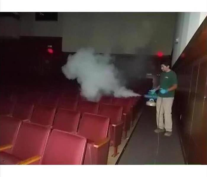 A SERVPRO employee spraying a fogger in a theater.