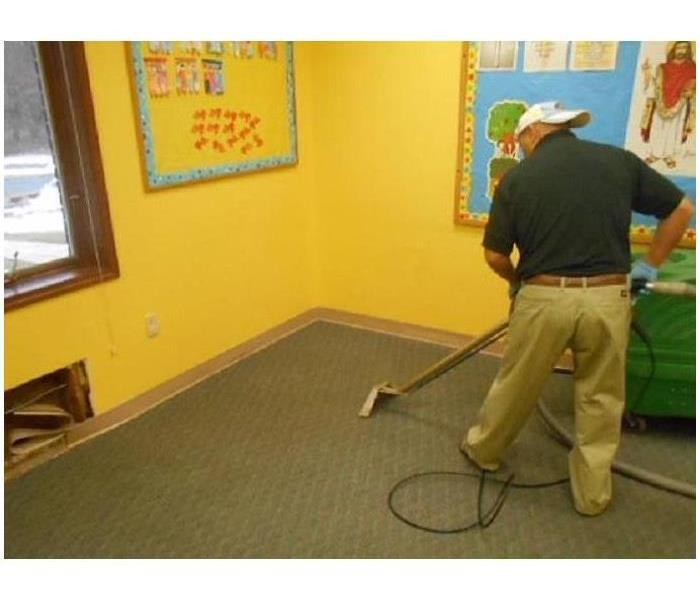 A man cleaning carpet in a room.
