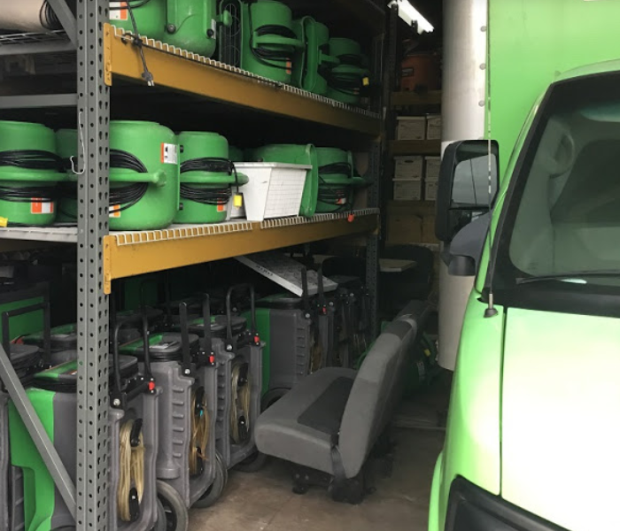 SERVPRO equipment on shelving next to a SERVPRO vehicle.