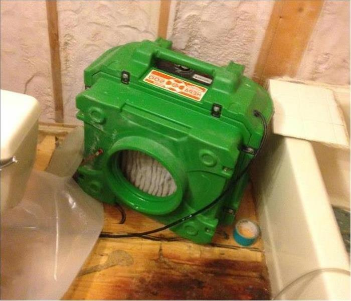 A bathroom floor with SERVPRO equipment on the floor.