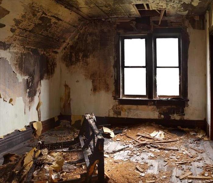 Fire damage to a room with windows.
